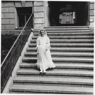 Dalia Grinkevičiūtė bei ihrer Kommunion, Foto Privatbesitz Vytene Muschick. Ein kleines Mädchen im weißen Kommunionskleid auf einer Treppe in Kaunas