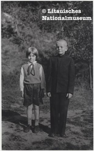 Dalia Grinkevičiūtė mit ihrem Bruder Juozas. 20 Jahrhundert, 30er Jahre.Besitz des Litauischen Nationalmuseums. Zwei Kinder stehen auf einem Weg, der Junge, einen Kopf größer, im schwarzen Anzug, das Mädchen in kurzen Hosen schaut selbstbewusst, aber zurückhaltend in die Kamera.